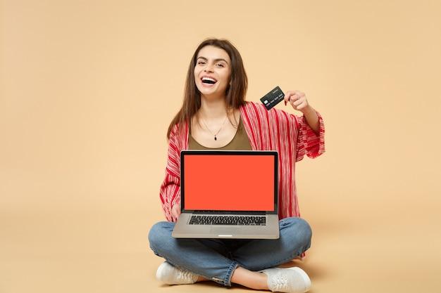 座って、クレジットバンクカード、パステルベージュの背景で隔離の空白の空の画面を持つラップトップpcコンピューターを持って笑う若い女性。人々の誠実な感情、ライフスタイルのコンセプト。コピースペースをモックアップします。