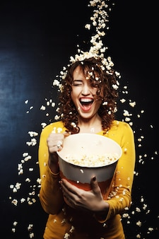 Laughing young woman staying under cheesy popcorn shower at cinema