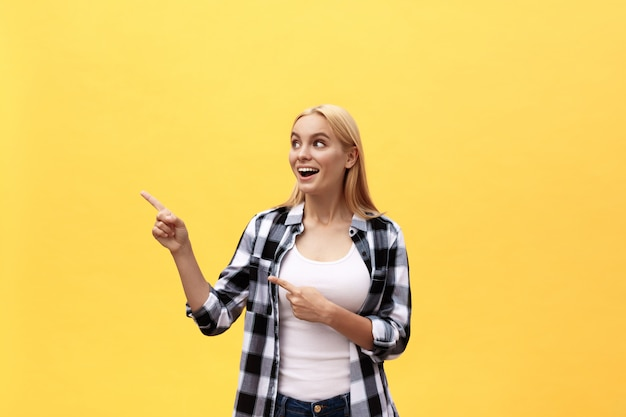 Laughing young woman in t-shirt looking and pointing away with thumb over yellow background