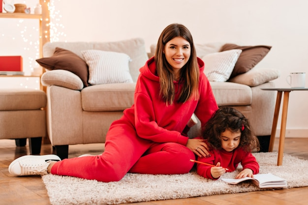 Ridendo giovane donna che insegna alla figlia a scrivere. tiro al coperto di felice madre e bambino seduto sul tappeto.