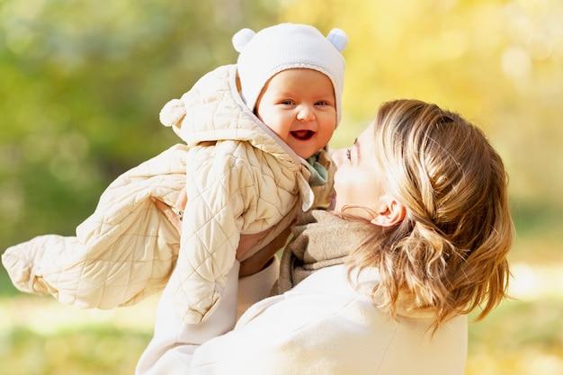 화창한 날 가을 공원에서 유아와 함께 웃고 있는 젊은 여성. 사랑과 부드러움. 확대.