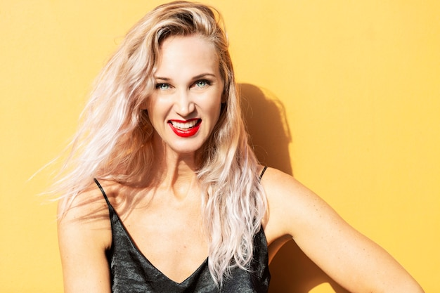 Laughing young woman on a yellow wall