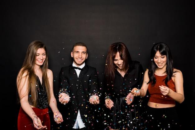 紙くずを投げつける夕方の服を着た若い女性と男性を笑う