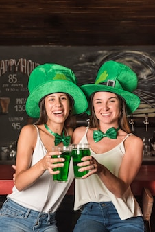 Смеющиеся молодые женщины в шляпах святого патрика, обнимающие и держащие стаканы с напитком у барной стойки