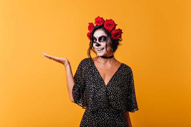 노란색 배경에 포즈 좀비 아가씨를 웃 고있다. 카메라에 미소 멕시코 할로윈 복장에 멋진 여성 모델.