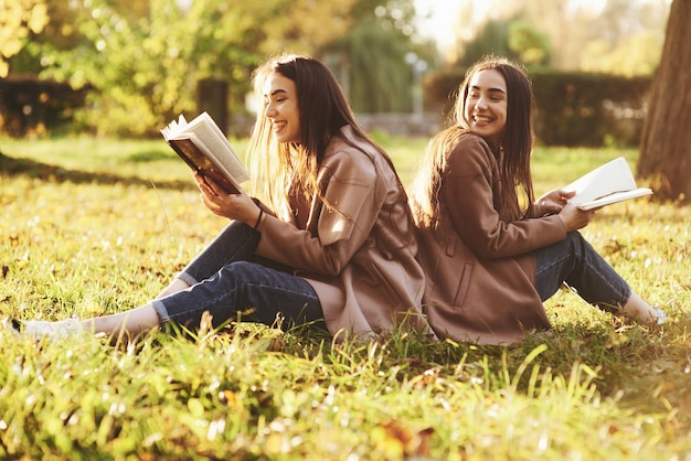 Laughinh brunette twin girls sitting back to back on the grass and having fun with legs slightly bent in knees, with brown books in hands, wearing casual coat in autumn park on blurry background.