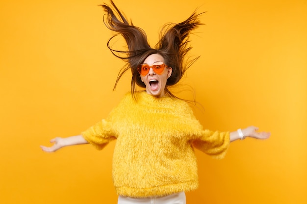 Laughter girl in fur sweater and heart orange glasses fooling around in studio jump with volant hair isolated on bright yellow background. people sincere emotions, lifestyle concept. advertising area.