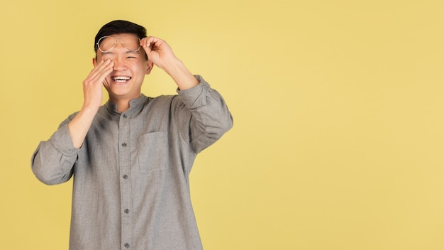 Laughting. asian young man's portrait on yellow  wall. handsome male model in casual style. concept of human emotions, facial expression, youth, sales, ad.