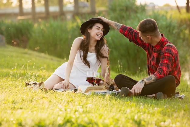 笑う。夏の日に公園で一緒に週末を楽しんでいる白人の若い、幸せなカップル