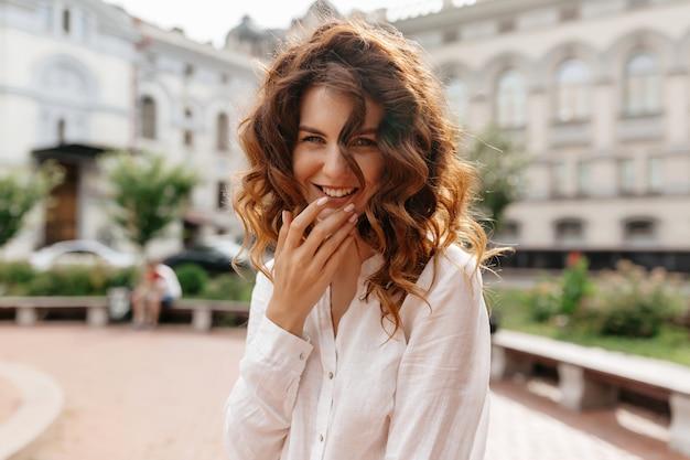 곱슬 머리를 가진 귀여운 여자를 웃음은 좋은 화창한 날에 도시에서 야외 산책하는 동안 좋은 시간을 보냅니다.