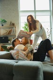 笑う。家で一緒に素敵な時間を過ごす家族は、幸せで陽気に見えます。枕で戦って楽しんでいるお母さん、お父さんと娘。一体感、家庭の快適さ、愛、関係の概念。