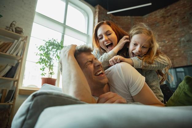 笑う。家で一緒に素敵な時間を過ごす家族は、幸せで陽気に見えます。お母さん、お父さん、娘がソファに横になって楽しんでいます。一体感、家庭の快適さ、愛、関係の概念。