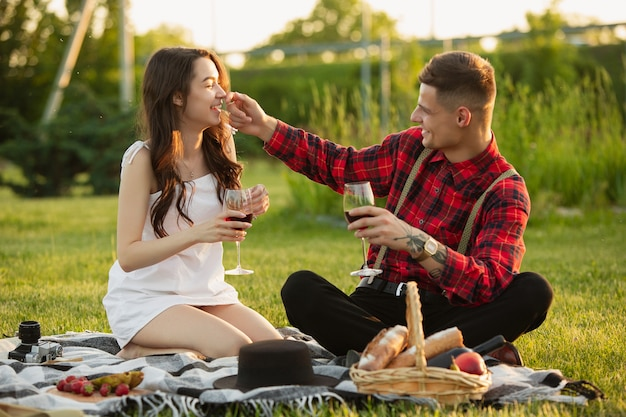 公園で一緒に週末を楽しんでいる白人の若いカップルを楽しんで笑う