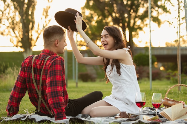Laughting, smiling. caucasian young couple enjoying weekend together in the park on summer day