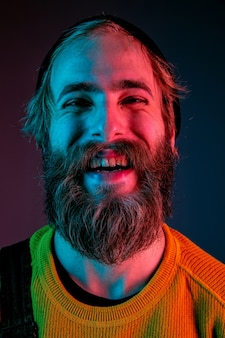 Laughting, smiling, close up. caucasian man's portrait on gradient studio background in neon light. beautiful male model with hipster style. concept of human emotions, facial expression, sales, ad.