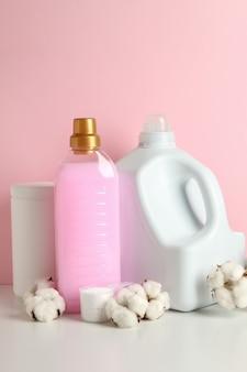 Аксессуары для стирки на белом столе против розового