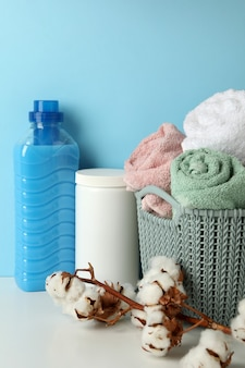 Laundry accessories on white table against blue background
