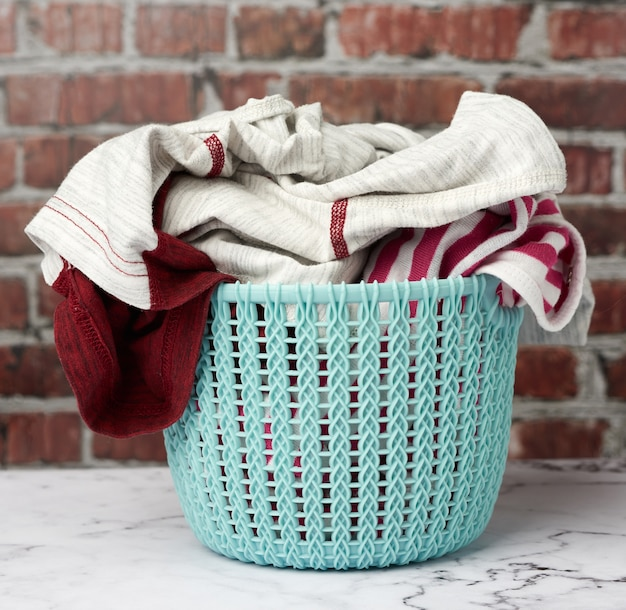 Laundry basket and folded laundry, brown brick wall