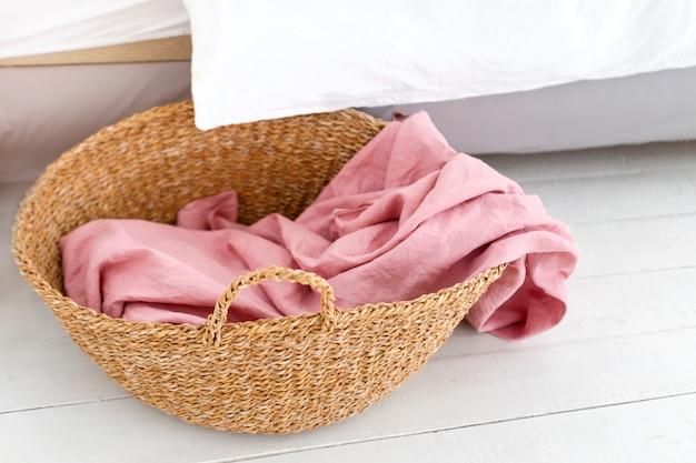 ピンクのタオルが付いている洗濯物入れ。ランドリーバスケットと白いスタイリッシュな部屋のインテリア