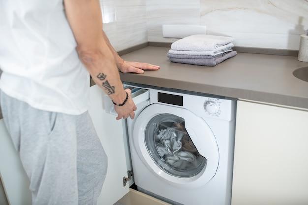 ランドリー。洗濯機を開く男の手の写真を閉じる
