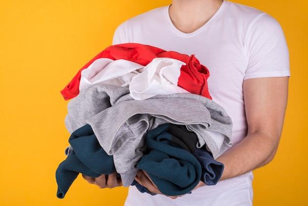 ランドリーのコンセプト。黄色の背景で隔離の服をたくさん持っている男の半分回転した写真をトリミング