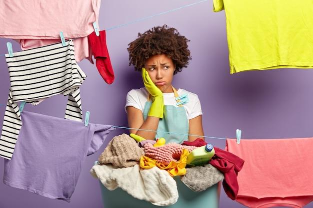 Concetto di giorno di lavanderia. la donna affaticata insoddisfatta tocca la guancia e distoglie lo sguardo infelice