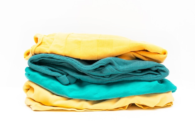 Laundry pile of colorful clothing isolated. stack of trendy color clothes close up.