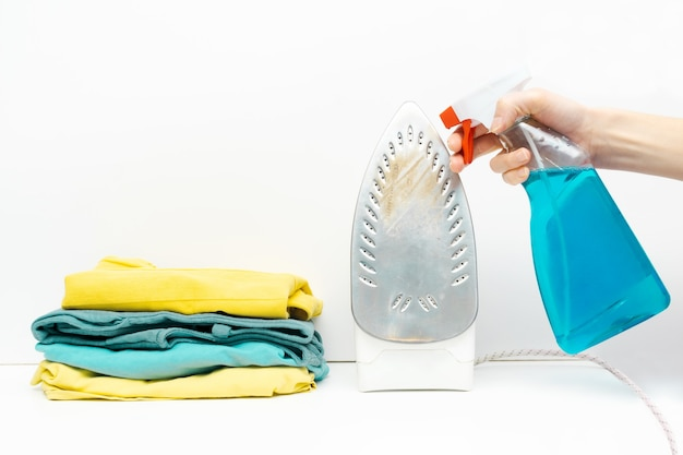 화려한 의류의 세탁 더미, 고립 된 옷의 스택, 병에 세제로 더러운 녹슨 철을 청소하는 여자.