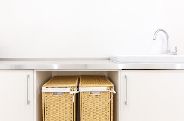 Laundry room in white modern style with baskets