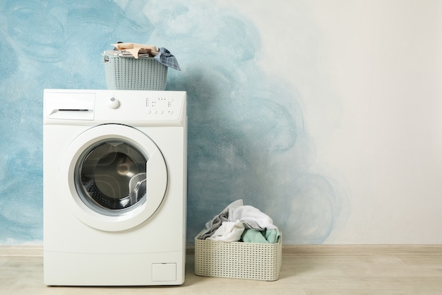 Laundry room with washing machine against blue wall, space for text