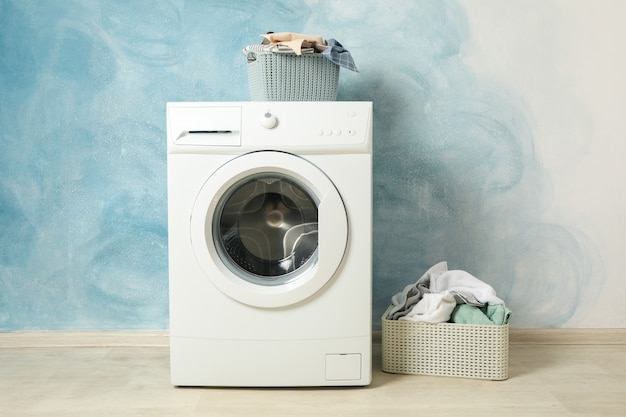 Laundry room with washing machine against blue wall