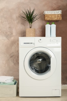 Laundry room with washing machine against brown wall
