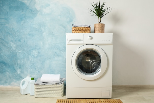 Laundry room with washing machine against light blue wall, space for text