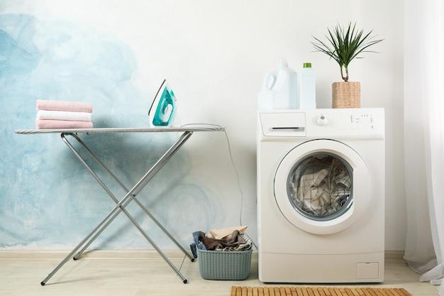 水色の壁に洗濯機付きのランドリールーム
