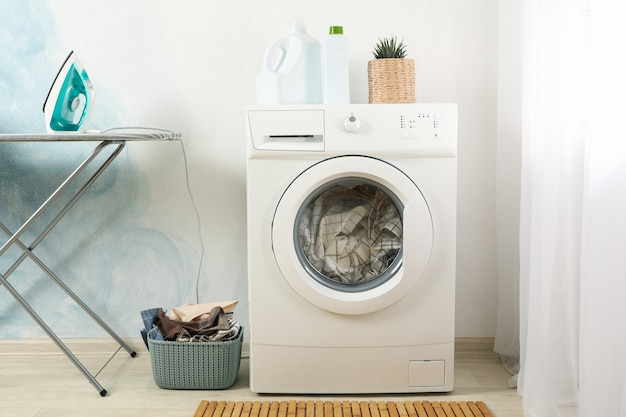 Laundry room with washing machine against light blue wall