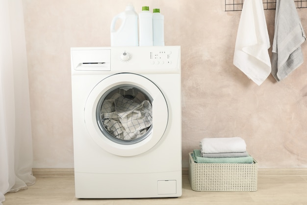 Laundry room with washing machine against light brown wall