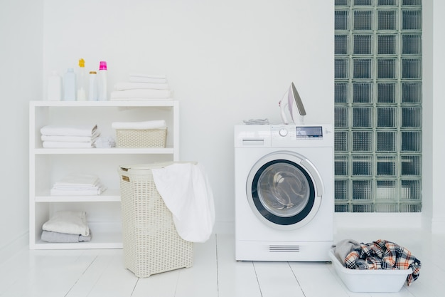 Laundry room with washing machine, dirty clothes in basket, iron and little shelf with neatly folded linen. domestic room interior. washing concept