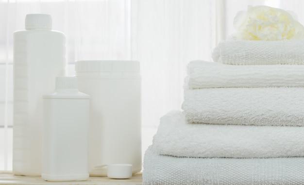 Бельё, белые контейнеры для моющих средств, макет и стопка белых полотен