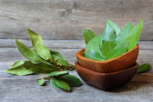 Laurel leaves in a wooden bowl on a gray kitchen table