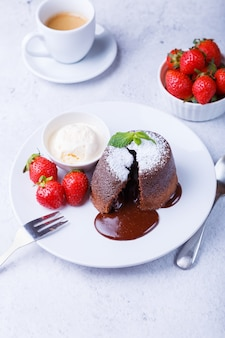 Lava cake - chocolate fondant cake with vanilla ice cream, strawberries, mint and coffee. traditional french pastries. close-up.