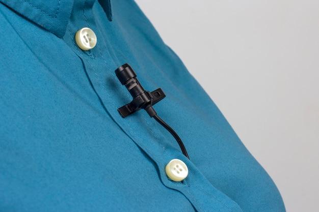 ラベリアマイクは、女性のシャツのクローズアップのクリップで固定されています。