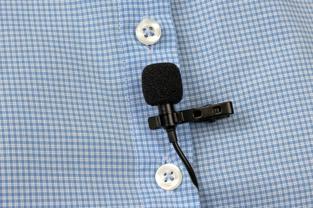 The lavalier microphone is secured with a clip on a shirt close-up.