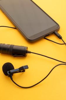 Петличный или петличный микрофон на цветной поверхности, подключенный к сотовому телефону, портретный вид.