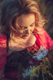 Красивая беременная женщина провансали ослабляя в поле лаванды наблюдая на заходе солнца держа корзину с цветками lavanda. серии. соблазнительная девушка с фиолетовой лавандой. блондинка в цветущем поле