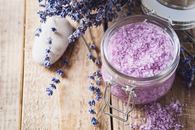 Лавандровая соль с натуральными спа-продуктами и декором для ванны на деревянном фоне