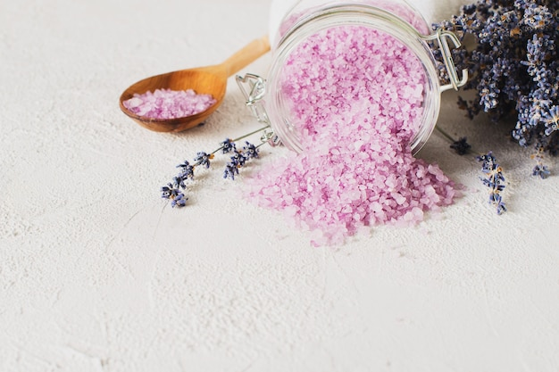 Lavander salt with natural spa products and decor for bath on grey background