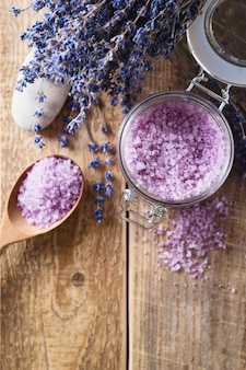 Lavander salt with natural spa products and decor for bath on wooden background
