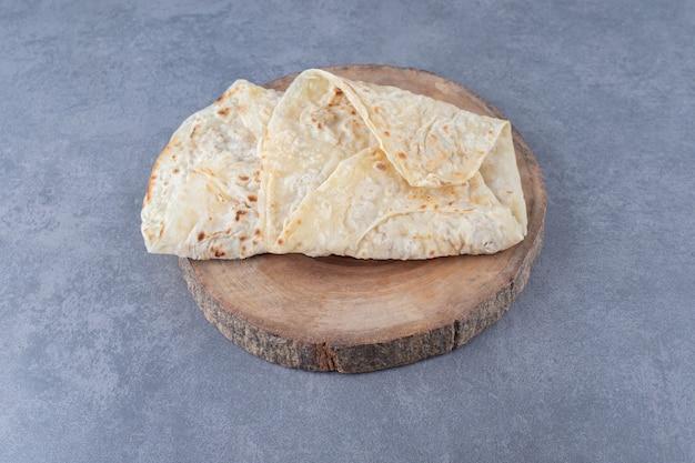 Хлеб из лаваша на доске на мраморном столе.