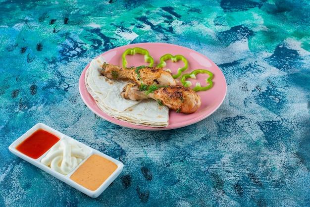 Lavash, cosce di pollo cotte e pepe su un piatto accanto alle ciotole di salsa sulla superficie blu