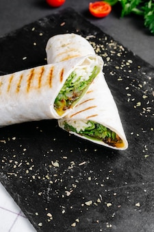 Lavash doner with lettuce and tomatoes on the table